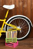 Bicycle with books in crate on wooden wall background