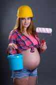 Happy Young Beautiful Pregnant Woman In Helmet With Builder's Tools Over Grey
