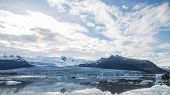 Glacier tonque and mountains in iceland, cloudy sky