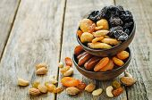 foto of mixed nut  - mix of dried fruits and nuts on a dark wood background - JPG