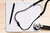 Notepad, pen and stethoscope against wooden surface - top view