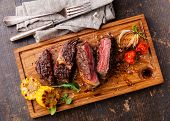 picture of bloody  - Sliced medium rare grilled Beef steak Ribeye with corn and cherry tomatoes on cutting board on wooden background - JPG
