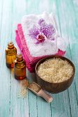 foto of salt-bowl  - Spa setting with sea salt soap towel and flower on aqua painted wooden boards - JPG