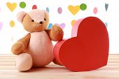 Teddy Bear with red heart on festive background