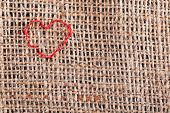 Linen canvas with red heart embroidered on it, close-up