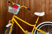 Bicycle with books on wooden wall background