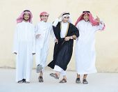 Happy group of Middle eastern Gulf boys dancing and celebrating party