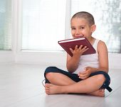 Happy cheerful child with book