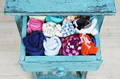 Socks in color drawer on wooden floor background