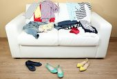 Colorful clothing on white sofa and female shoes