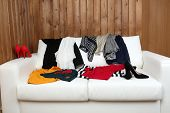 Messy clothing with shoes on white sofa, on wooden planks  background