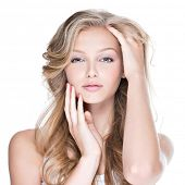 Portrait of beautiful young woman with long curly hair touching her face - isolated on white.