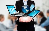 Businesswoman holds laptop, phone, tablet, globe in hands. Office Background - Stock Image