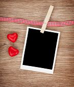Blank instant photo with candy hearts. On wooden background