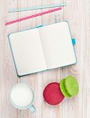 Cup of milk and macarons on white wooden table with notepad for copy space