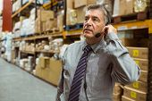 Focused businessman talking in a headset in a large warehouse