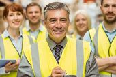 Warehouse team with arms crossed wearing yellow vest in a large warehouse