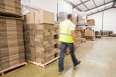 Blurred manual worker walking in the warehouse