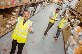 picture of warehouse  - Warehouse manager smiling at camera showing thumbs up in a large warehouse - JPG