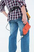 Rear view of male handyman holding drill machine over white background