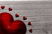 Red love hearts against digitally generated grey wooden plank