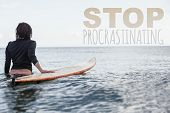 Rear view of a woman with surfboard in the water against stop procastinating
