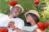 Happy couple lying in garden together on the grass against cute valentines message