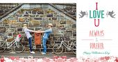 Hip young couple dancing by brick wall with their bikes against i love you message
