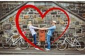 Hip young couple dancing by brick wall with their bikes against heart
