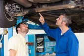 Mechanic showing customer the problem with car at the repair garage
