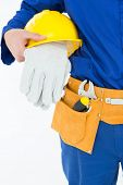 Cropped image of repairman holding helmet and gloves against white background