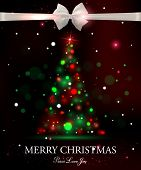 Merry Christmas typographical celebration concept with silk white bow and shining christmas tree.