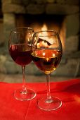 Wine Glasses on the tablecloth. Fireplace Background