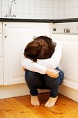 Lonely depressed woman sitting on kitchen floor.