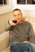 Mature man with remote control relaxing in living room