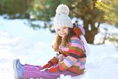 Little Child Sitting On The Snow Having Fun In The Winter Day