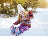 Little Child Sitting On The Snow Having Fun In Winter