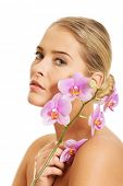 Beautiful spa woman with purple orchid flower.