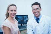 Portrait of smiling male dentist and woman against computer