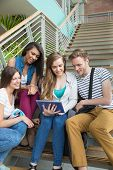 Smiling students sitting on steps with tablet pc at the university
