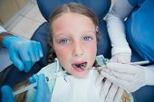 Dentist with assistant examining girls teeth in the dentists chair