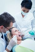 Close up of male dentist with assistant examining womans teeth in the dentists chair
