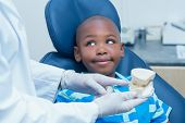 picture of prosthesis  - Cropped dentist showing young boy prosthesis teeth in the dentists chair - JPG