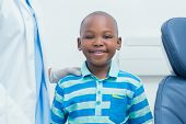 Portrait of smiling young boy standing by cropped dentist