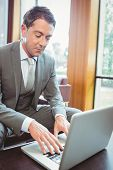 Focused handsome businessman using his laptop in the office