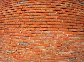 stock photo of fragmentation  - Fragment of old and red brick wall with wide angle fisheye lens and distortion view - JPG