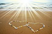 stock photo of two hearts  - Seashell hearts on sandy beach with sunbeams