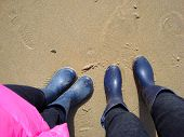 image of woman boots  - legs of a little girl and a young woman standing on wet beach sand in blue boots - JPG