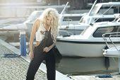 stock photo of marina  - Stylish woman in dungarees standing on marina - JPG