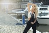 picture of dungarees  - Stylish woman in dungarees standing on marina - JPG